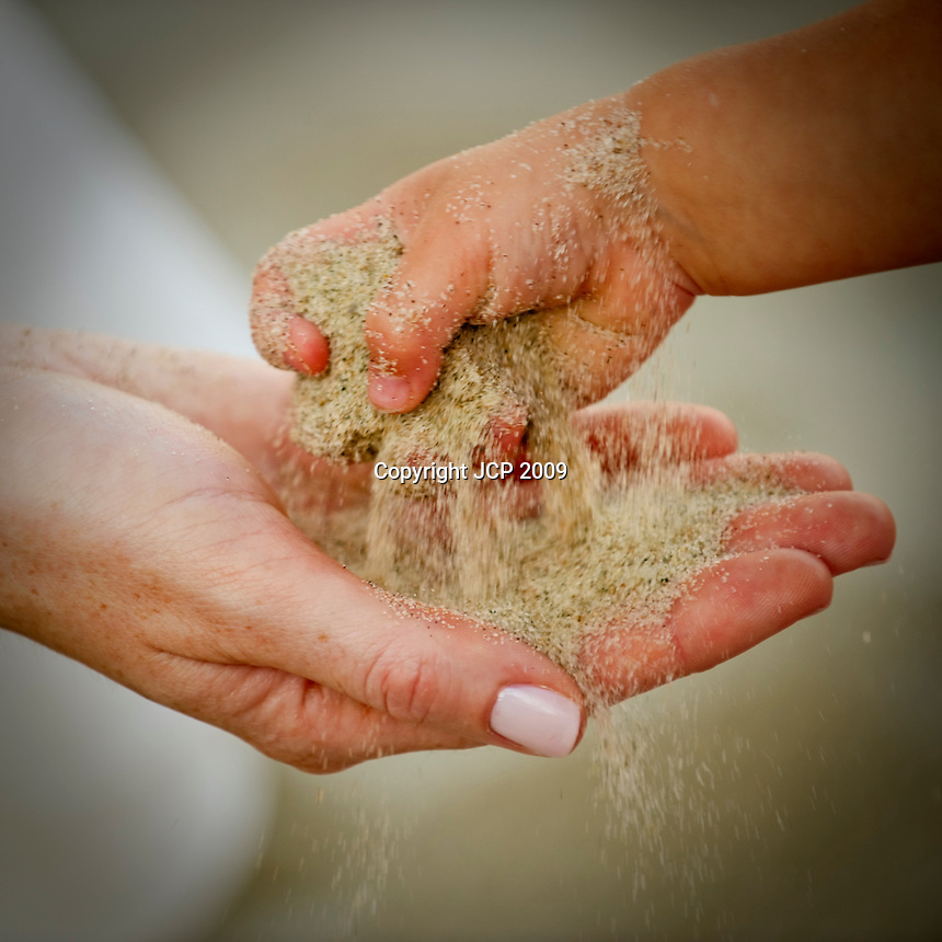 A little girl putting sand in the bride's hand