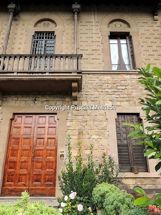 Antella, Italy - October 2, 2012:  A Tuscan townhouse has wooden doors and balcony.
