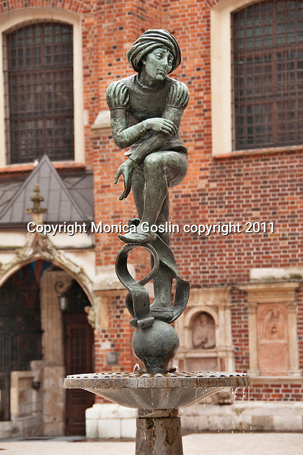 A statue and fountain in the small square by St. Mary's Church in Krakow, Poland
