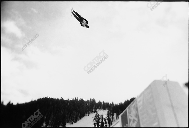 With sun bouncing off the clouds in Park City, Utah, an Aerial Skier takes flight off the jump in front of 14000 spectators at the 2002 Olympic Winter Games.