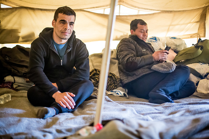 Makeshift tent camp at the serbian side of the border where the conatiner camp being built in hugary. Three afgani and one nepali men waiting in one of the tents. They are on the waiting list, (only five applicants processed per day). At some point an unidentified man is stepping out from the gate to the hungarian side and giving them some food packages. Tea from milk is being made in the tent. They use whatever they find to feed the fire in the fireplace (rubbish, worn chlotes, scrap wood).