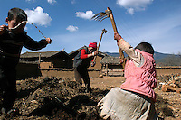 Jaka Duzhelum, 37, and her twin daughters aerate a manure pile in preparation for spring planting. The family lost their home to a fire and struggle to maintain the fields while rebuilding the house by hand.