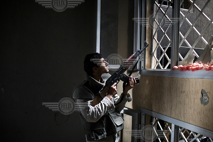 A rebel fighter stands at a window as he fights Gaddafi forces in central Misurata. On 17 February 2011 Libya saw the beginnings of a revolution against the 41 year regime of Col Muammar Gaddafi.Hours later Guy Martin was seriously injured in an RPG attack.