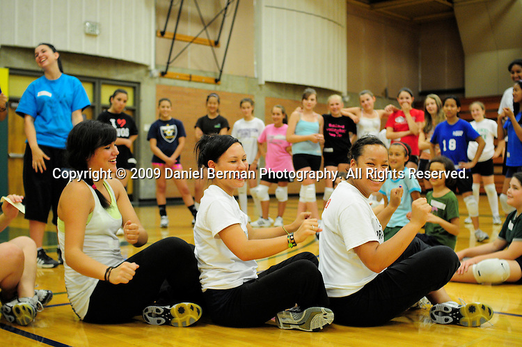 "Daniel Berman/Special to The Enterprise..Shoreline CC volleyball players Katie Dapper, Sydney Hinnebusch, and Shelbey Souther laugh as they show participants how to perform a warm-up exercise called ""row the boat"" during a youth volleyball camp held Monday July 27 at Shoreline Community College...Shoreline, WA"