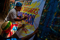 """A Colombian sign painter paints letters on a hand-painted promotional banner in the sign painting workshop in Cartagena, Colombia, 14 April 2018. Hidden in the dark, narrow alleys of Bazurto market, a group of dozen young men gathered around José Corredor (""""Runner""""), the master painter, produce every day hundreds of hand-painted posters. Although the vast majority of the production is designed for a cheap visual promotion of popular Champeta music parties, held every weekend around the city, Runner and his apprentices also create other graphic design artworks, based on brush lettering technique. Using simple brushes and bright paints, the artisanal workshop keeps the traditional sign painting art alive."""
