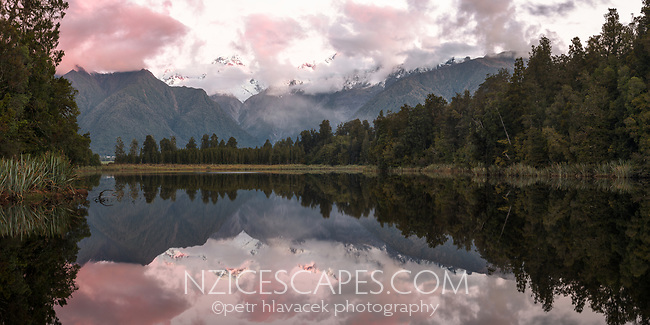 Sunset over Lake Matheson with clouds and perfect reflections, Westland Tai Poutini National Park, UNESCO World Heritage Area, West Coast, New Zealand, NZ