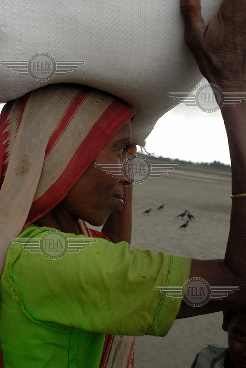 Shanti, a widow and mother of two, carries home the 28 kilo food package she has received from the Bangladesh Red Crescent Society aid cards after her village on the Oshdomi Chor (a small river island) was submerged by severe flooding..