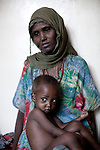 WAJIR, KENYA - JULY 6: Makay Bashane, age 40, with her child Abdirahim Abdullah, age two, waits to be weighed and measured after being admitted to the stabilization center in Wajir on July 6 in central Wajir, Kenya. The children were referred to the stabilization center in Wajir by Save the Children. Two successive poor rains, entrenched poverty and lack of investment in affected areas have pushed millions of people into a fight for survival in the Horn of Africa. This is the driest this area has been since sixty years. People in smaller town are usually fortunate to have water. In rural areas, most wells has dried up and some people was as much as eight kilometers to fetch water. Most of the livestock has perished and the remaining stock has often been taken far away for better conditions. Many has even crossed into neighboring Somalia for better pasture. (Photo by Per-Anders Pettersson)