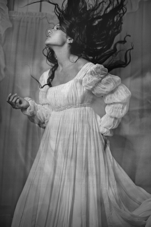 A slender, dark haired, spanish woman in a long flowing dress tosses her head backwards, causing her hair to flow above and behind her as her face turns up toward the ceiling.