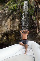 Man enjoys a refreshing waterfall shower from the bow of a boat, Amalfi Coast, Italy