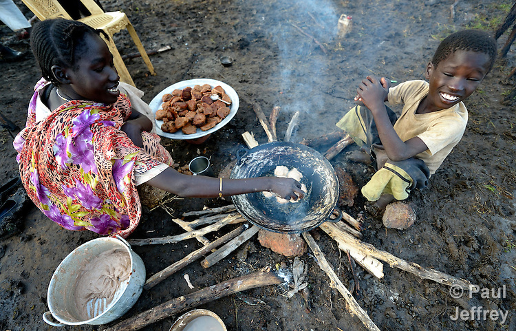 A mother cooks breakfast while her son evades the smoke in the Gendrassa refugee camp in South Sudan's Upper Nile State. More than 110,000 refugees were living in four camps in Maban County in October 2012, but officials expected more would arrive once the rainy season ended and people could cross rivers that block the routes from Sudan's Blue Nile area, where Sudanese military has been bombing civilian populations as part of its response to a local insurgency. Conditions in the camps are often grim, with outbreaks of diseases such as Hepatitis E.