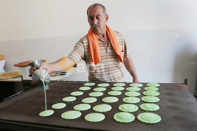 "A Palestinian man prepares traditional pancakes known as ''Qatayef"" at his shop during the Muslim holy fasting month of Ramadan in the West Bank village of Ein Yabrud near Ramallah on June, 21, 2016. Ramadan is sacred to Muslims because it is during that month that tradition says the Koran was revealed to the Prophet Mohammed. The fast is one of the five main religious obligations under Islam. More than 1.5 billion Muslims around the world will mark the month, during which believers abstain from eating, drinking, smoking and having sex from dawn until sunset. Photo by Shadi Hatem"
