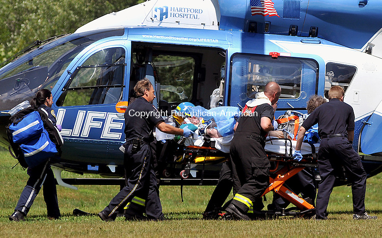 LITCHFIELD, CT, 26 JULY 2011-072611JS03-- Emergency personnel transport a patient to a waiting Life Star helicopter Tuesday at Alain White Field in the Bantam section of Litchfield. The patient had smoke inhalation as well as burns from a kitchen fire at a home on Circle Drive in Bantam. <br /> Jim Shannon/Republican-American