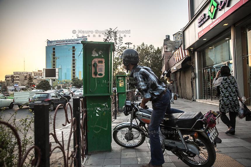 Teheran, un motociclista si avvicina a un posto telefonico