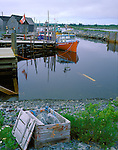 Queens County, Nova Scotia<br /> Weathered crate sits on the shoreline of an inner Harbor with moored fishing boats and boat houses at Blueberry Bay, village of West Berlin