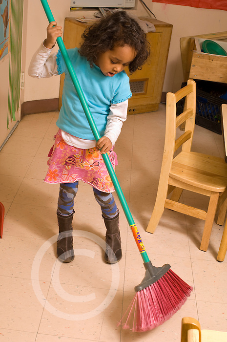Preschool classroom New York City  classroom chore girl using broom to sweep floor vertical Hispanic American