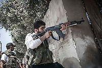 An opposition fighter targets with his Kalashnikov to the sniper position as Free Army rebels repel an offensive attack by Assad's army during a battle in the neighborhood of Jaser Al Nerab. Intensive combats have taken place in the area under control of the rebels close to the airport to regain the position lost by the Assad's troops.