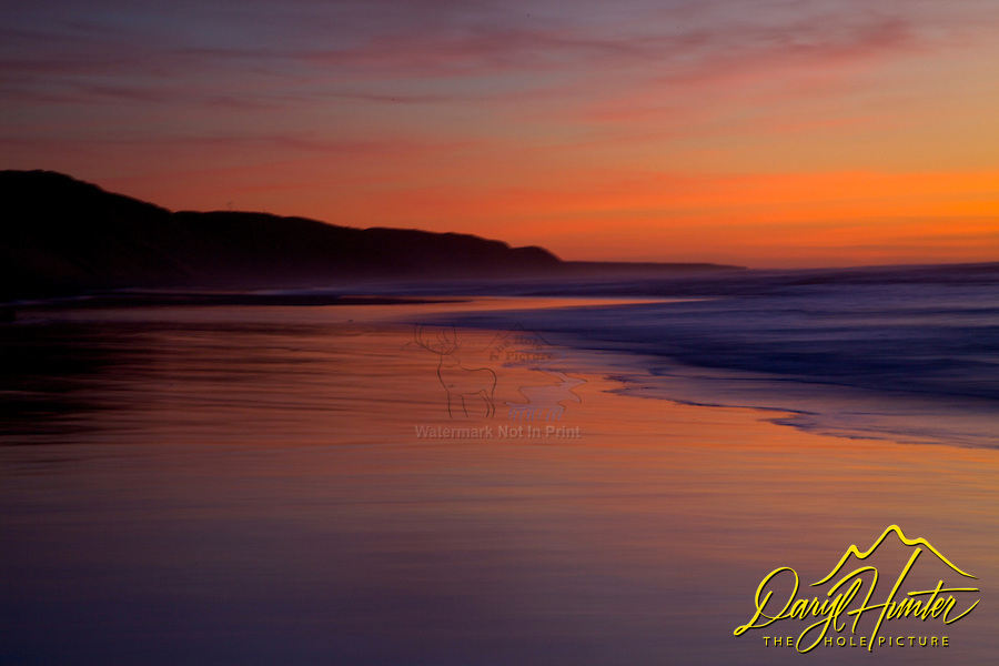 Bright orange sky at sunset on the beach in Morro Bay, California