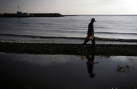 A man walks on the shores of Qinghai Lake. Qinghai Lake, China's largest inland body of water lies at over 3000m on the Qinghai-Tibetan Plateau. The lake has been shrinking in recent decades, as a result of increased water-usage for local agriculture. Qinghai Province. China. 2010