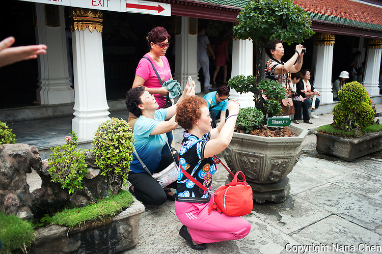 Most travelling out of the country for the first time, a group of middle-aged Chinese tourists point their cameras around the Grand Palace in Bangkok, one of the most popular attractions in the Thai capital.