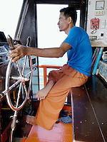 Thailand. Trat province. Mature ship captain at the helm of the diving boat on the way to Ko Rang island. Bare feet. Ko Rang island is a natural park. 11.04.09 © 2009 Didier Ruef