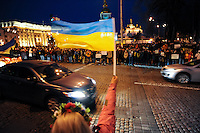 A demonstrator wave an Ukrainian flag  in front of the nearby Mykhailiv monastery where people regathered  to continue the  protest  after the violent repression  on main square performed by the riot police, Kiev.