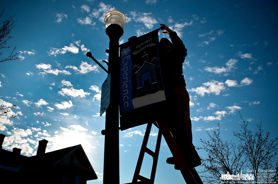 A Westerville OH electrical worker removes the last of city's Christmas decorations from a light pole in Uptown.