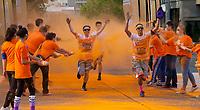 Man Running Through Orange Dye Color Zone, Seattle Center, Washington State, WA, America, USA.