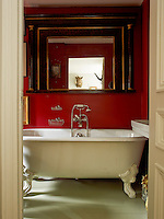 A boar's head hanging on the wall of the master bedroom is reflected in the tortoiseshell-framed mirror above the roll top bath in the en-suite bathroom