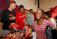 NWA Media/DAVID GOTTSCHALK - 12/12/14 - Semaj (cq) Franklin, 12, receives a ham from University of Arkansas Razorback basketball players Nick Babb , left, and Michael Qualls Friday December 12, 2014 at the Donald W. Reynolds Boys and Girls Club in Fayetteville. Members of the basketball team and staff represented the University of Arkansas Student Athletes as they partnered with the Dwelling Place and the Donald W. Reynolds Boys and Girls Club in distributing 99 hams to children and families at the club.