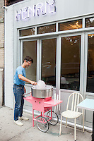 Andr&eacute; Saraiva makes cotton candy in front of the new Cafe Henri in Chinatown. <br /> <br /> Danny Ghitis for The New York Times