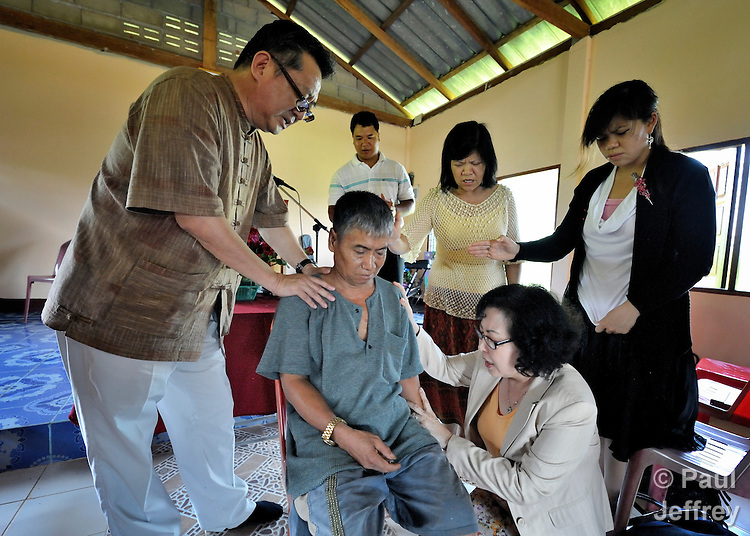 Gary Moon (left) and his wife Cindy (kneeling), United Methodist missionaries in Thailand, pray over Todo Phrabinyan in the Pranetta United Methodist Church in Buyer, a small village in northern Thailand populated by indigenous hill tribe people. Phrabinyan is recovering from a stroke.