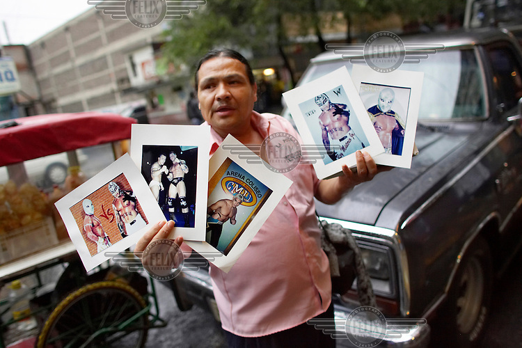 A man sells pictures of famous Luchadores (fighters) outside the Arena Mexico before a Lucha Libre match. Lucha Libre is a style of wrestling started in Mexico in 1933. The name means Free Fight, and matches tend to be focussed on spectacle and theatre with fans cheering for their favourite characters, who wear masks while jumping from the ropes, flipping opponents, and occasionally crashing into the crowd..