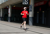 9th May 2020, Emirates  Stadium, London, England; Male runner exercising outside the Emirates Stadium  during the Covid-19 lockdown