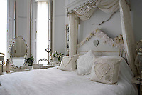 The half-tester bed is adorned with pretty cushions and a white bed cover