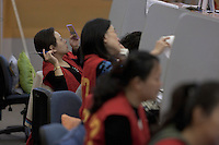 A woman dealer trims her eyebrows at Shanghai Stock Exchange in Shanghai, China on November 9, 2009.