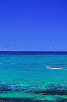 View of blue sky & ocean with small boat on right side in waters off Lanikai.