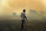 A man gestures around the area where a fire burns in Cualedro, near Ourense, on August 10, 2010. (c) Pedro ARMESTRE