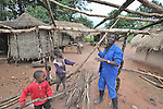 A man in Dundube Kadambo, in northern Malawi, builds a hut with help from his two sons.