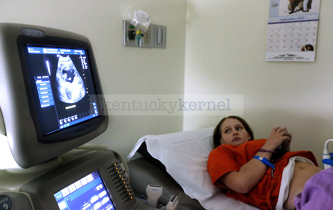 "Amanda Driggers watches as a picture of her 3-month-old baby is pulled up on the scree in the Kentucky River Medical Center. She watched in silence and finally asked, ""What's going to happen to my baby?"" Photo by Britney McIntosh"