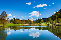 Oesterreich, Tirol, bei Fieberbrunn: der auf 859 m Hoehe gelegene Lauchsee ist ein Moorsee mit einer Badegelegenheit Moorbad Lauchsee, im Hintergrund die schneebedeckten Leonganger Steinberge (links) und die Kitzbueheler Alpen mit Spielberghorn (2.044 m) | Austria, Tyrol, near Fieberbrunn: moorlake Lauchsee with Leonganger Steinberge mountains (left) and Kitzbuehel Alps with summit Spielberghorn (2.044 m)