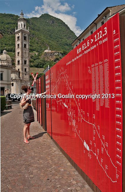 A woman looks at a map detailing the path of the Bernina Express in Tirano, Italy with the Madonna di Tirano Basilica in the background