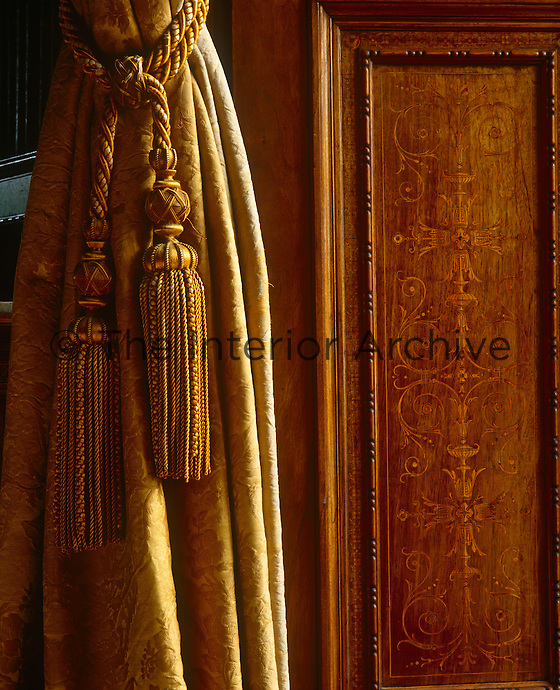 Close up of a gold-coloured curtain tassel on a damask curtain next to an inlaid door panel