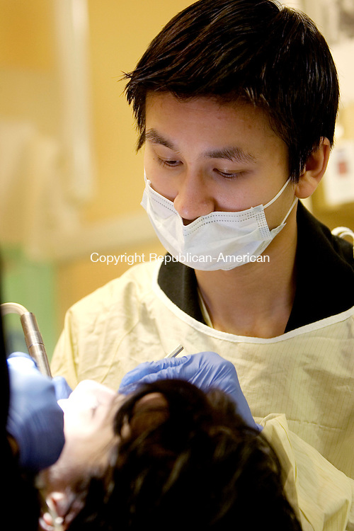 WATERBURY, CT. 05 February 2011-020511SV09--Dr. Edward Xu, of the St. Mary&rsquo;s Hospital Dental Program, works on a patent during the Gives Kids a Smile Day at the StayWell South End Health Center in Waterbury Saturday.<br /> Steven Valenti Republican-American