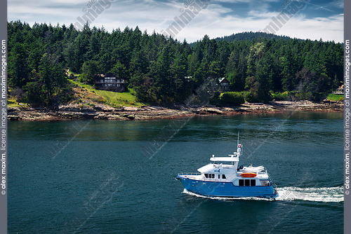 Motor yacht boat going past Galiano Island one of Southern Gulf Islands near Vancouver Island of British Columbia, Canada