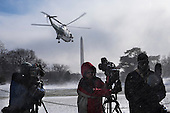 Members of the media turn away from the blowing snow as Marine One comes in for a landing on the snow covered South Lawn of the White House in Washington, District of Columbia, U.S., on Wednesday, Jan. 7, 2015.  United States President Barack Obama is traveling to the Ford Michigan Assembly Plant in Wayne, Michigan to deliver remarks highlighting the workers in the resurgent American automotive and manufacturing sector now that the auto rescue has been completed and the decision to save the auto industry and the over one million jobs that went with it. Photographer: Pete Marovich/Bloomberg/POOL<br /> Credit: Pete Marovich / Pool via CNP