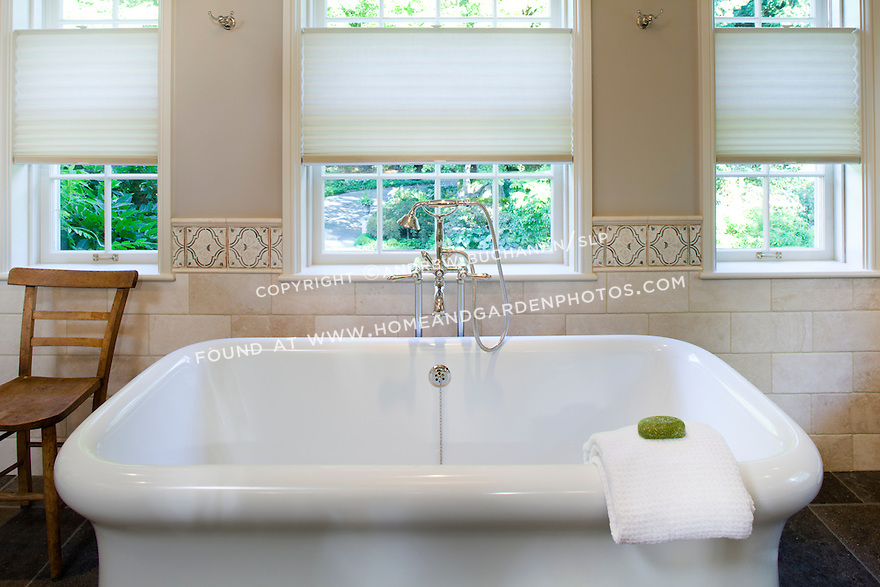 A freestanding bathtub with decorative tile wall behind