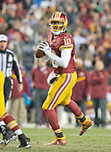 Washington Redskins quarterback Robert Griffin III looks for a receiver in third quarter action against the Philadelphia Eagles at FedEx Field in Landover, Maryland on Saturday, December 20, 2014.  The Redskins won the game 27 - 24.<br /> Credit: Ron Sachs / CNP