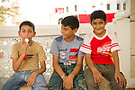 Three boys enjoy some time in the shade at the Mutrah Souk in Muscat, Oman