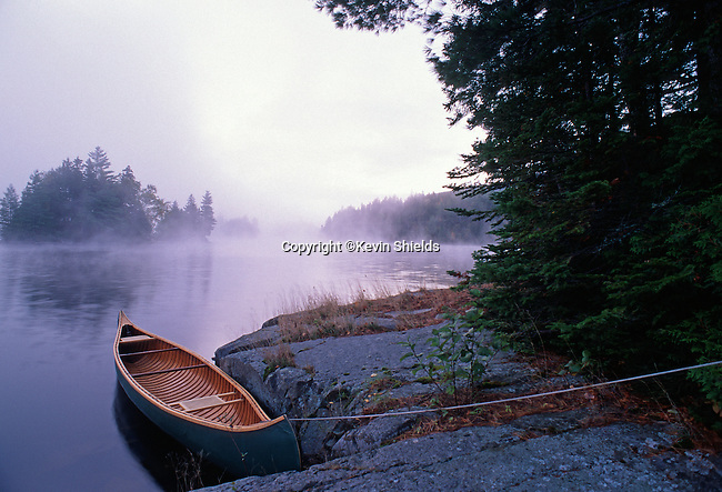 Canoe tied to shore at dawn, Chain of Ponds Township, Maine, USA
